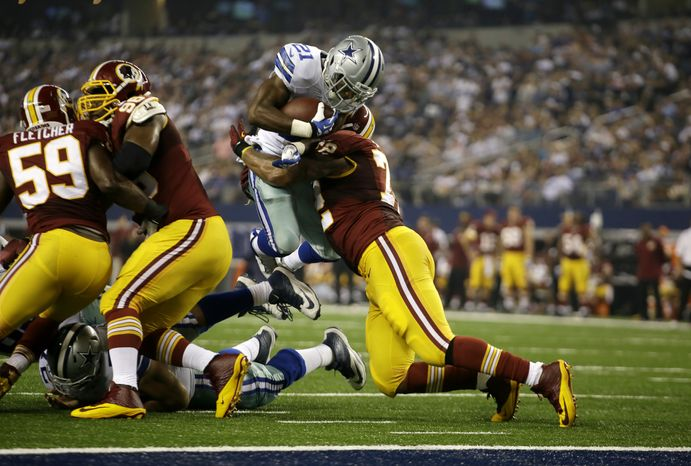 Dallas Cowboys running back Joseph Randle (21) is stopped by Washington Redskins defensive end Stephen Bowen (72) in the second half of an NFL football game, Sunday, Oct. 13, 2013, in Arlington, Texas. (AP Photo/Tim Sharp)