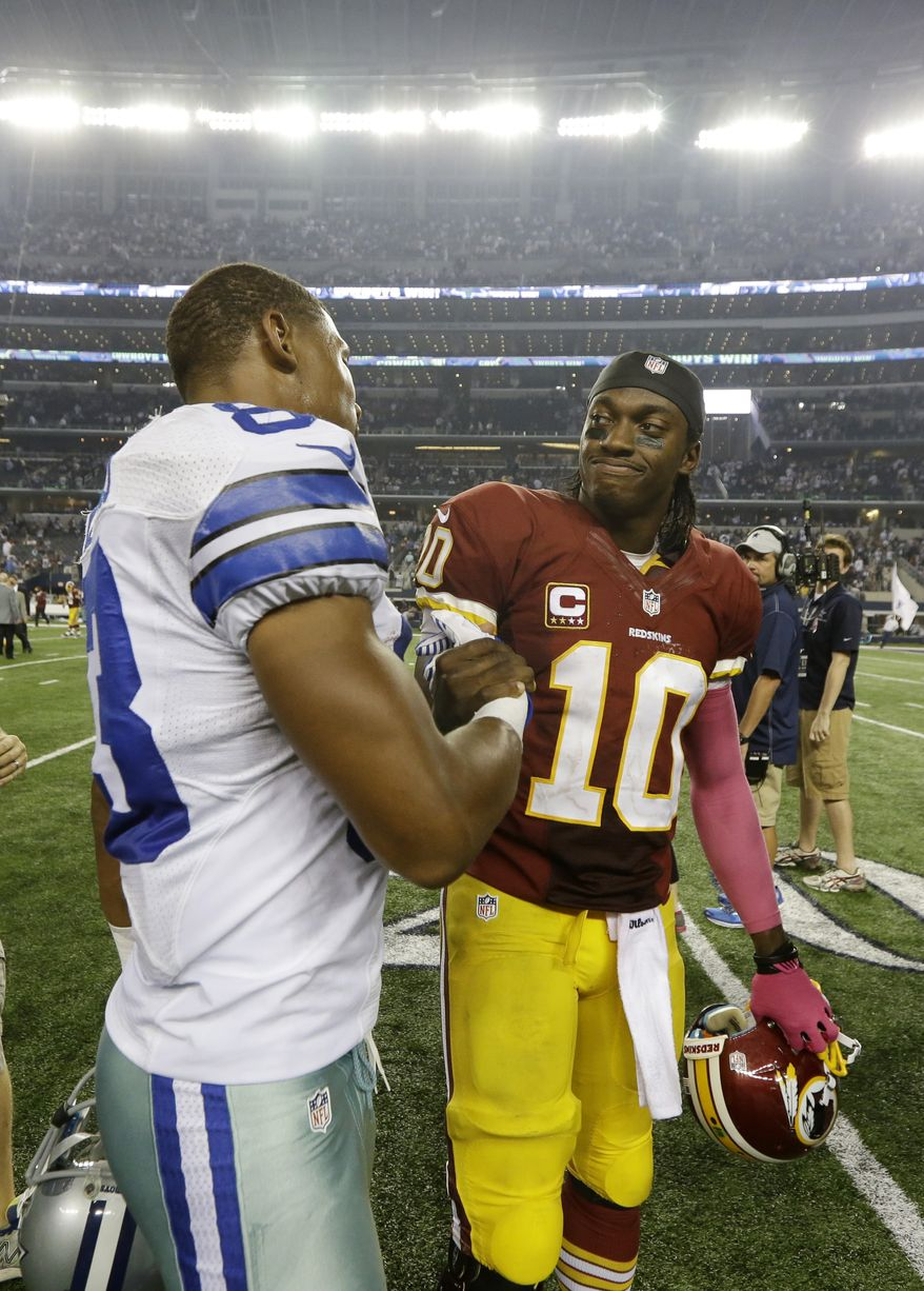 Dallas Cowboys wide receiver Terrance Williams (83) greets Washington Redskins quarterback Robert Griffin III (10) after an NFL football game, Sunday, Oct. 13, 2013, in Arlington, Texas. The two players were teammates at Baylor before playing in the NFL. (AP Photo/LM Otero)