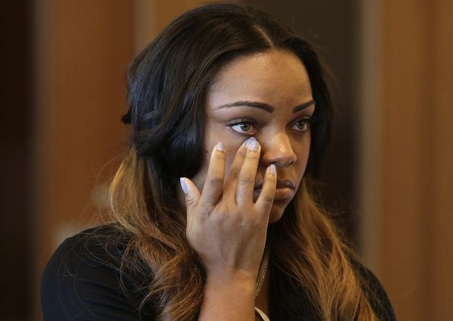 Shayanna Jenkins, girlfriend of former New England Patriots' Aaron Hernandez, wipes her eye in superior court, in Fall River, Mass., Tuesday, Oct. 15, 2013, during her arraignment on a perjury charge in connection with the killing of Hernandez's friend. Authorities say Jenkins, 24, was untruthful in her testimony before the grand jury investigating the death of Odin Lloyd. (AP Photo/Steven Senne, Pool)