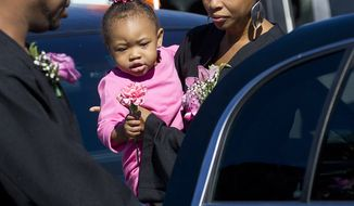 Amy Carey-Jones, sister of Miriam Carey, exits Grace Funeral Chapels with her daughter, Nyimah Jones, after the funeral for Miriam Carey in the Brooklyn borough of New York,  on Tuesday, Oct. 15, 2013.  Carey was shot to death by police after trying to ram her vehicle through a White House barrier. (AP Photo/The Stamford Advocate, Lindsay Perry)