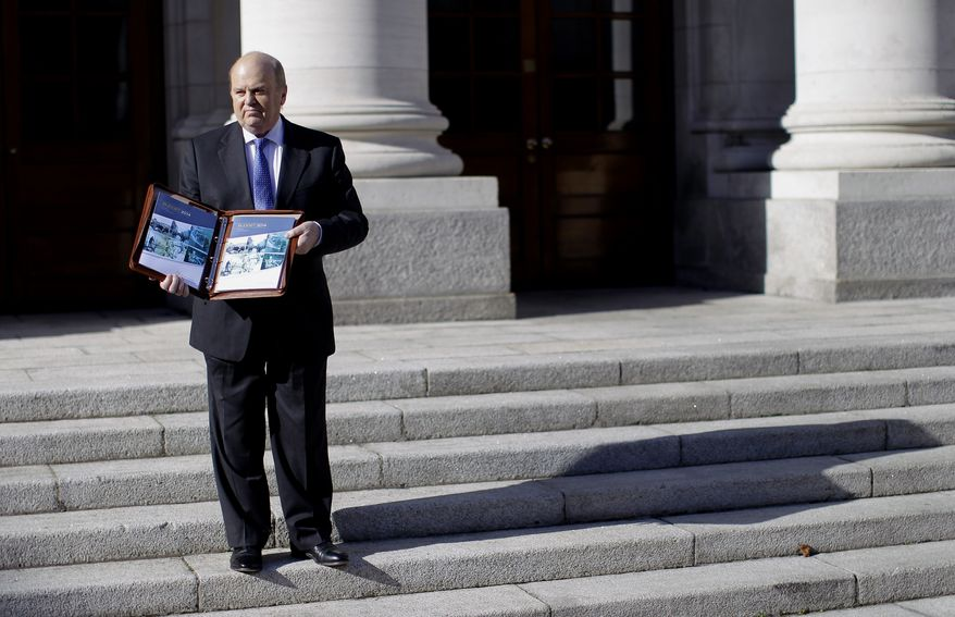 Minister for Finance Michael Noonan poses with the Budget 2014 on the steps of government building's, Dublin, Ireland, Tuesday, Oct. 15, 2013. Irish finance minister Michael Noonan is expected to unveil another tough budget Tuesday. Noonan and the Public Expenditure Minister, Brendan Howlin, will take a further 2.5bn euros (£2.1bn) out of the Republic of Ireland's economy. It is the last budget before the country leaves its EU-IMF bailout programme on 15 December. (AP Photo/Peter Morrison)