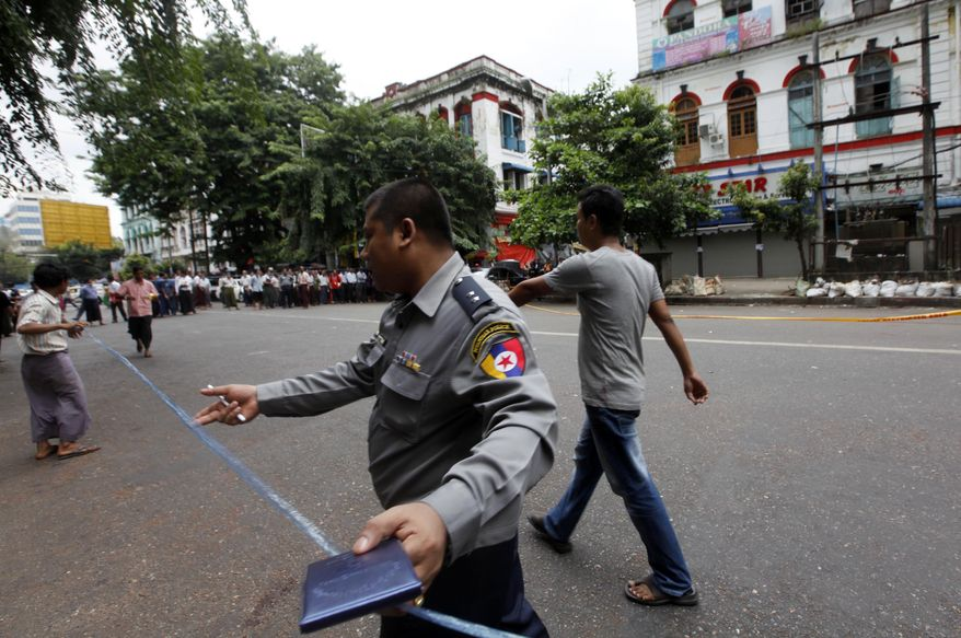 A Myanmar policeman seals off an area after a bomb squad found a suspicious looking packet in downtown Yangon, Myanmar, Tuesday, Oct. 15, 2013. Police urged vigilance after several small bombs exploded in and around Myanmar's largest city of Yangon in recent days. No one claimed responsibility for the boasts and it was not immediately clear if they were related. (AP Photo/Khin Maung Win)