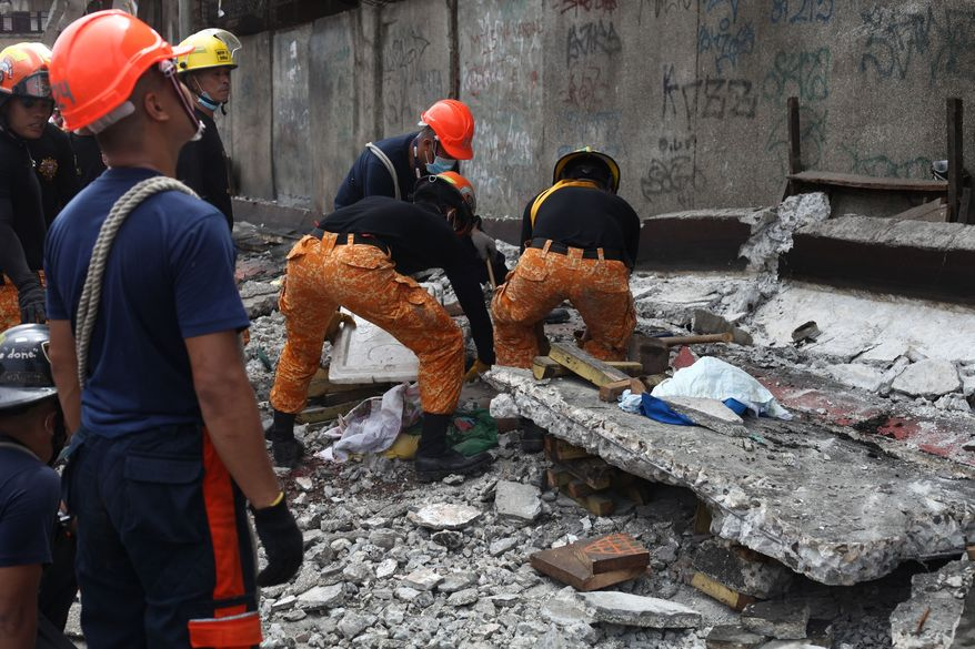 Rescuers shift through the rubble to recover an unidentified man at a fish port in Pasil, Cebu, central Philippines on Tuesday Oct. 15, 2013. A 7.2-magnitude earthquake collapsed buildings, cracked roads and toppled the bell tower of the Philippines' oldest church Tuesday morning, killing at least 20 people across the central region. (AP Photo/Chester Baldicantos)