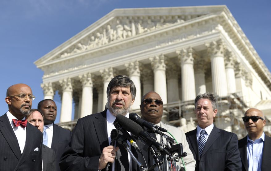 Mark Rosenbaum, center, of the American Civil Liberties Union, speaks to reporters after arguing their case before the Supreme Court in Washington, Tuesday, Oct. 15, 2013. The high court is considering a case centered around a 2006 Michigan vote that approved a ballot initiative amending the state's constitution to ban affirmative action programs in higher education. (AP Photo/Susan Walsh)