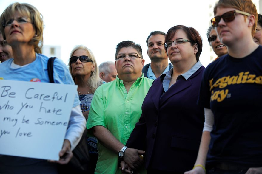 Jayne Rowse (third from left) holds hands with her partner, April DeBoer, during a rally outside the federal courthouse in Detroit. The couple initially intended to file a lawsuit that would allow them to adopt each other's children, but ended up challenging Michigan's ban on gay adoption and same-sex marriage. (associated press)