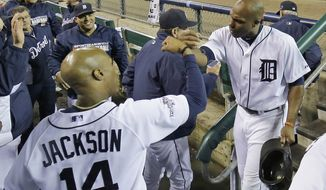 Detroit Tigers' Torii Hunter is congratulated by Austin Jackson after Hunter scored in the second inning after scoring on a single by Miguel Cabrera during Game 4 of the American League baseball championship series Wednesday, Oct. 16, 2013, in Detroit. (AP Photo/Matt Slocum)