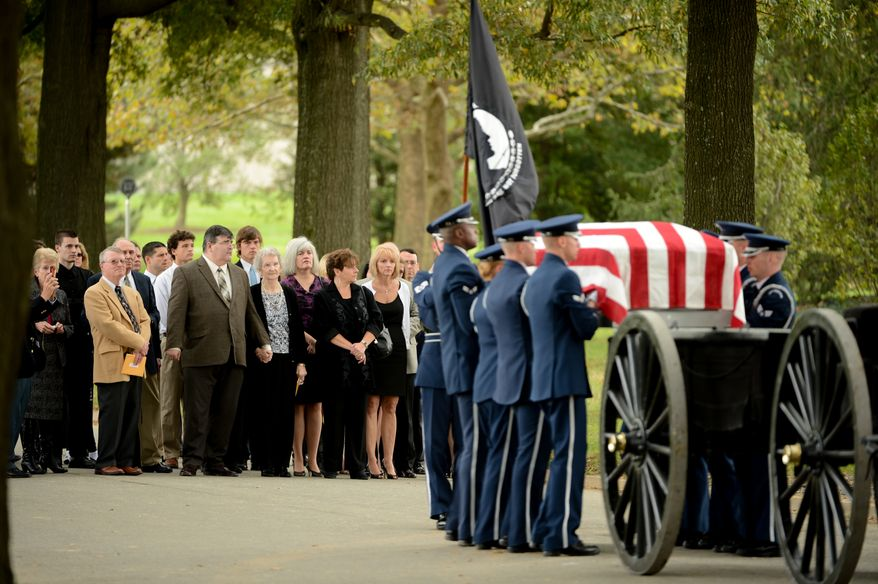 Family and friends including Audrey Fitzgerald, the widow to Lt. Col. Robert Pietsch, forth from right, and David Pietsch, the son of Lt. Col. Robert Pietsch, fifth from right, watch as a casket team carries a single casket for Air Force Lt. Col. Robert Pietsch and Air Force Maj. Louis Guillermin, airmen from the Vietnam War during a burial service at Arlington National Cemetary, Arlington, Va., Wednesday, October 16, 2013. (Andrew Harnik/The Washington Times)