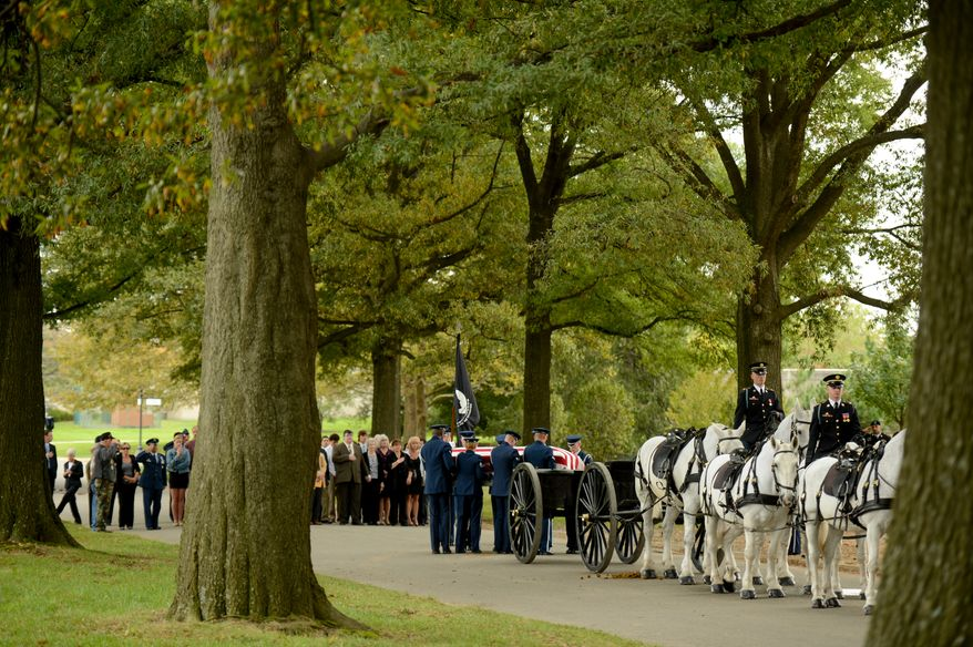 Family and friends watch as a casket team carries a single casket for Air Force Lt. Col. Robert Pietsch and Air Force Maj. Louis Guillermin, airmen from the Vietnam War during a burial service at Arlington National Cemetary, Arlington, Va., Wednesday, October 16, 2013. (Andrew Harnik/The Washington Times)