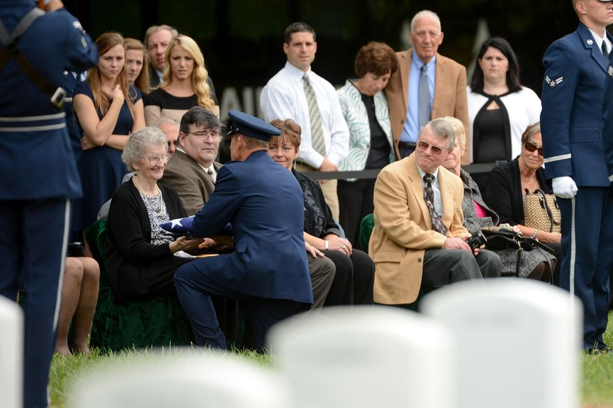 Audrey Fitzgerald, the widow to Lt. Col. Robert Pietsch, left is presented with an American flag by U.S. Air Force Lt. Gen. Michael Basla during the funeral of Air Force Lt. Col. Robert Pietsch and Air Force Maj. Louis Guillermin, airmen from the Vietnam War at Arlington National Cemetary, Arlington, Va., Wednesday, October 16, 2013. (Andrew Harnik/The Washington Times)