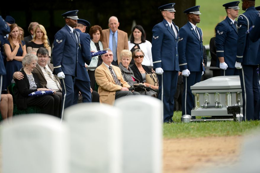 Audrey Fitzgerald, the widow to Lt. Col. Robert Pietsch, left is comforted by her son, David Pietsch, second from left, after recieving an American flag by U.S. Air Force Lt. Gen. Michael Basla during the funeral of Air Force Lt. Col. Robert Pietsch and Air Force Maj. Louis Guillermin, airmen from the Vietnam War at Arlington National Cemetary, Arlington, Va., Wednesday, October 16, 2013. (Andrew Harnik/The Washington Times)