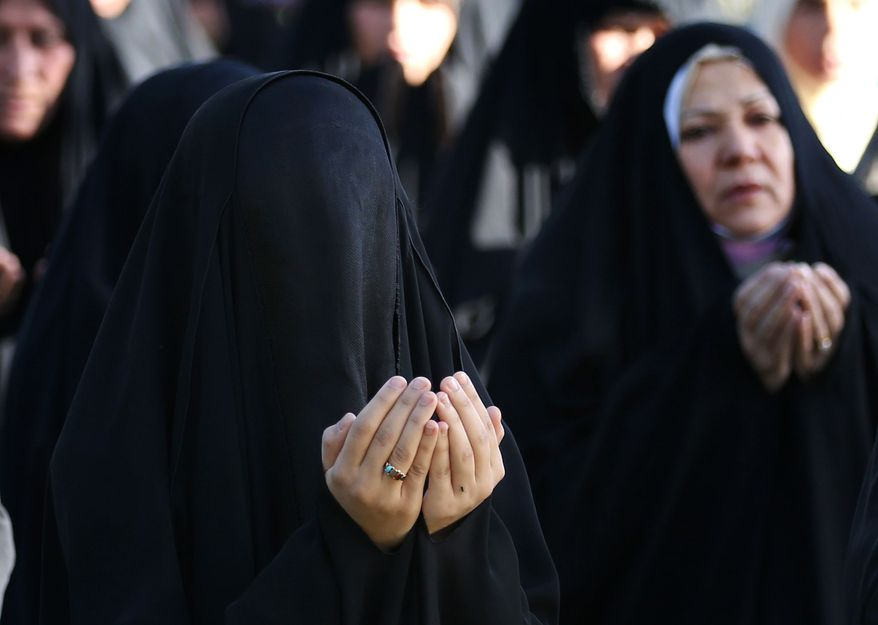 Iraqi Shiite Muslim women attend the Eid al-Adha prayer, outside the party headquarters of the Supreme Islamic Council, in Baghdad, Iraq, Wednesday, Oct. 16, 2013. Muslims all over the world are celebrating Eid al-Adha by sacrificing sheep, goats, cows and camels, to commemorate the Prophet Abraham's readiness to sacrifice his son, Ismail, on God's command. (AP Photo/Hadi Mizban)