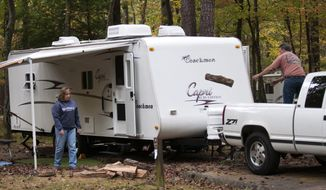 "Earl and Pam Robinson of Chatsworth, Ga., are among the first to get settled into the newly reopened Cades Cove campground in the Great Smoky Mountains National Park near Townsend, Tenn., on Wednesday, Oct. 16, 2013,  The couple have been camping in the Smokies for 23 years and had made reservations six months ago for this trip. ""I could hug the governor's neck, "" said Earl about the reopening of the park. The Tennessee state government and Sevier and Blount counties are paying over $300,000 for five days of operation costs for the park which has been closed due to the partial federal government shutdown. North Carolina is adding $75,000. (AP Photo/Knoxville News Sentinel, Paul Efird)"