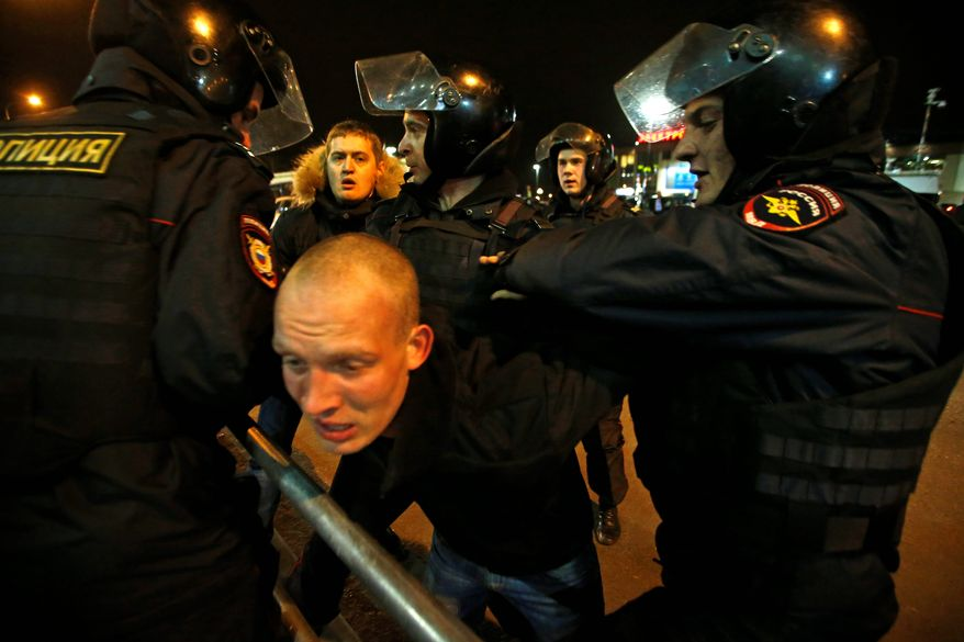 Police detain a Russian nationalist protester this week at a Moscow subway station as tensions in the country rise amid a wave of hate-crimes against migrants, mostly from the Caucasus. (Associated Press)