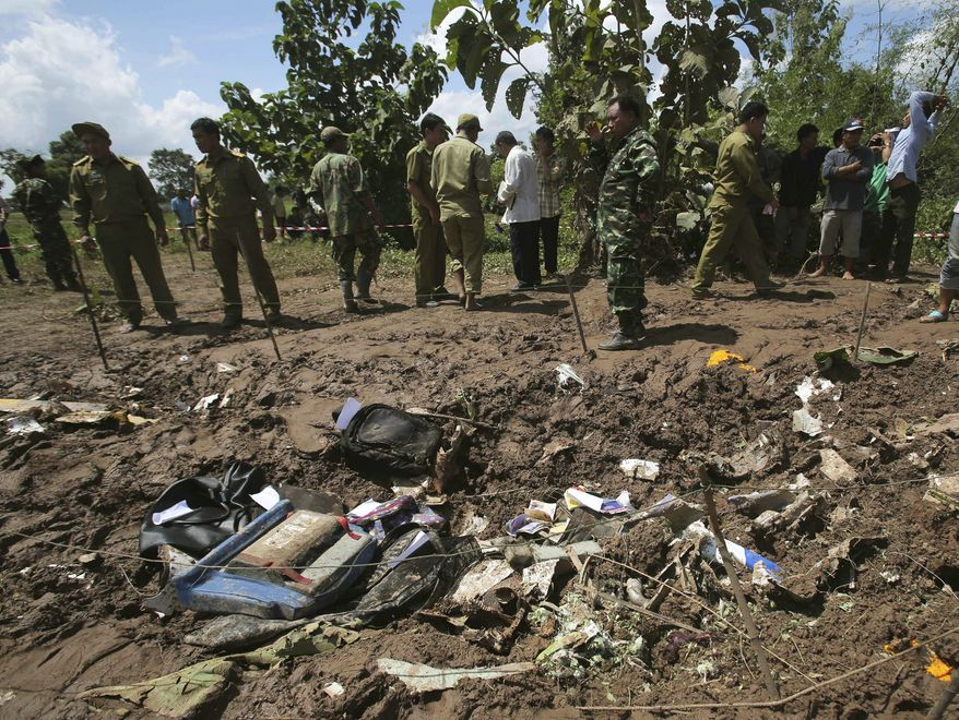 Lao soldiers and policemen work on Thursday, Oct. 17, 2013, at the scene where a Lao Airlines turboprop plane hit hard before skidding into the Mekong River in Pakse, Laos, on Wednesday. The aircraft crashed after running into extremely bad weather conditions; all 49 people on board were killed. (AP Photo/Sakchai Lalit)