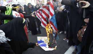 In this Friday, Nov. 2, 2012, file photo, Iranian female demonstrators burn a representation of U.S. flag, and a caricature of President Barack Obama, in an annual state-backed rally in front of the former U.S. Embassy in Tehran, Iran, commemorating 33rd anniversary of the embassy takeover by militant students. (AP Photo/Vahid Salemi, File)