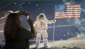 A woman takes a photograph of a mural at the Smithsonian's Air and Space Museum in Washington, Thursday, Oct. 17, 2013. Barriers went down at federal memorials, National Park Service sites, as well as the Smithsonian Institution's network of popular museums and thousands of furloughed federal workers returned to work across the country Thursday after 16 days off the job due to the partial government shutdown. (AP Photo/Cliff Owen)