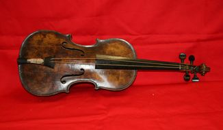 "This is an undated handout image from auction house Henry Aldridge and Son made available on Friday Oct. 18, 2013 shows a  violin believed to be the one played by Titanic bandmaster Wallace Hartley will now go on auction.   It's a poignant scene familiar to anyone who has watched ""Titanic""  as the ship slides into the icy waters, musicians perform for the passengers, playing with stoic resolve until the final hour. None of the musicians survived in the 1912 disaster in the North Atlantic. The auction house, which specializes in Titanic memorabilia, expects the violin to fetch more than 200,000 pounds (US$323,300) when it goes on sale Saturday Oct 19, 2013. (AP Photo/Henry Aldridge and Son)"