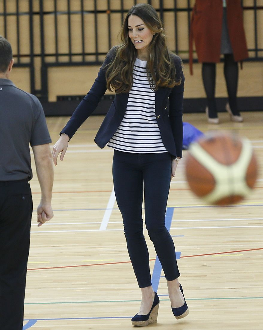 Britain's Kate, The Duchess of Cambridge tours a sports hall during a visit to a SportsAid Athlete Workshop, at the Queen Elizabeth Olympic Park in London, Friday, Oct. 18, 2013. The Duchess of Cambridge as Patron of SportsAid attended a SportsAid Athlete Workshop at the Copper Box where she viewed young athletes taking part in a number of sports activities. (AP Photo/Kirsty Wigglesworth)