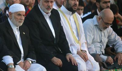 Gaza's Hamas Prime Minister Ismail Haniyeh, center, prays on the first day of  Eid al-Adha  in Al-Yarmouk Stadium in Gaza City, Tuesday, Oct. 15, 2013. Muslims worldwide are celebrating Eid al-Adha, or the Feast of the Sacrifice, by sacrificial killing of sheep, goats, cows or camels. The slaughter commemorates the biblical story of Abraham, who was on the verge of sacrificing his son to obey God's command, when God interceded by substituting a ram in the child's place. (AP Photo/Hatem Moussa)