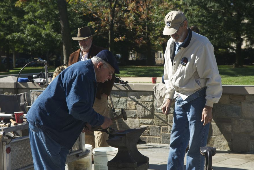 """An event based on the theme of """"beating swords into plowshares"""" had religious and secular leaders taking hammers to gun parts that blacksmiths had turned red from heat outside the Washington National Cathedral on Sunday, Oct. 20, 2013, in Washington."""
