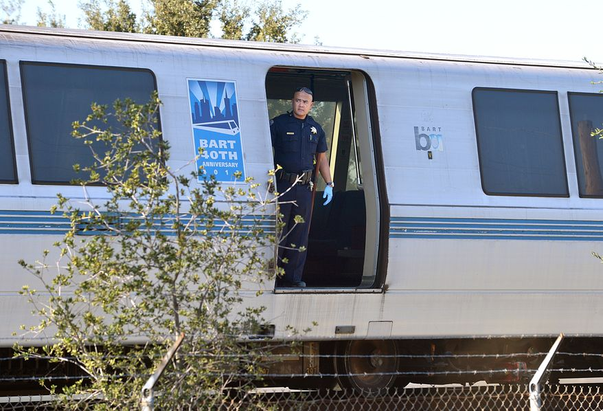 A Bay Area Rapid Transit police officer looks out from a car of a train that struck and killed two workers along Jones Road in Walnut Creek, Calif., on Saturday, Oct. 19, 2013. (AP Photo/The Mercury News, Dan Rosenstrauch)