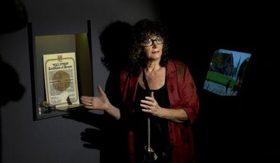 """Irena Steinfeldt, an official at Israel's Yad Vashem Holocaust memorial, shows a certificate recognizing Dr. Mohamed Helmy, an Egyptian physician in Berlin, as """"Righteous Among the Nations"""" for saving a Jewish family during the Holocaust, in Jerusalem on Monday, Sept. 30, 2013. (AP Photo/Sebastian Scheiner)"""