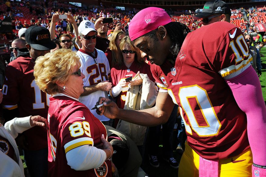 Washington Redskins quarterback Robert Griffin III (10) signs an autograph before the game at FedExField, Landover, Md., October 20, 2013. (Preston Keres/Special for The Washington Times)