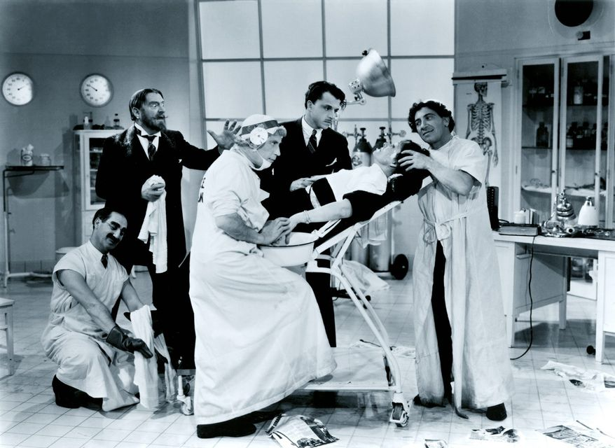 """The Marx Brothers tend to Margaret Dumont's medical needs in a scene from """"A Day at The Races"""""""