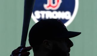 """With a """"B strong"""" emblem on the Green Monster wall in honor of the Boston Marathon bombing surviviors, Boston Red Sox's Dustin Pedroia holds a bat during team baseball practice at Fenway Park in Boston, Monday, Oct. 21, 2013. The Red Sox are preparing to face the St. Louis Cardinals in Game 1 of the World Series on Wednesday. (AP Photo/Elise Amendola)"""