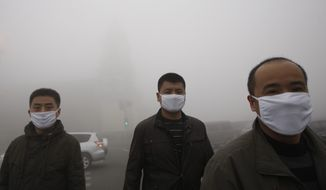 Chinese men walk on the street during a day of heavy pollution in Harbin, in northeast China's Heilongjiang province, on Monday, Oct. 21, 2013. Visibility shrank to less than half of a football field, and small-particle pollution soared to a record 40 times higher than an international safety standard in the city as the region entered its high-smog season. (AP Photo)