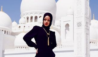 "In this photo posted to an Instagram account belonging to Rihanna, pop star Rihanna poses for a photo in front of Abu Dhabi's Grand Mosque in the United Arab Emirates. Overseers of Abu Dhabi's Grand Mosque say they asked Rihanna to leave the compound after she posed for photographs considered to be at odds with the ""sanctity"" of the site. Rihanna, who was in the city for a concert on Saturday, Oct. 19, 2013, hasn't publicly responded to the actions by staff at the Sheikh Zayed Grand Mosque. (AP Photo/via Instagram)"