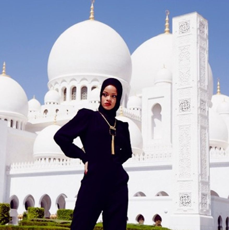 """In this photo posted to an Instagram account belonging to Rihanna, pop star Rihanna poses for a photo in front of Abu Dhabi's Grand Mosque in the United Arab Emirates. Overseers of Abu Dhabi's Grand Mosque say they asked Rihanna to leave the compound after she posed for photographs considered to be at odds with the """"sanctity"""" of the site. Rihanna, who was in the city for a concert on Saturday, Oct. 19, 2013, hasn't publicly responded to the actions by staff at the Sheikh Zayed Grand Mosque. (AP Photo/via Instagram)"""