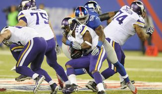 Minnesota Vikings running back Adrian Peterson, front, is tackled by New York Giants outside linebacker Jon Beason (52) during the second half of an NFL football game Monday, Oct. 21, 2013 in East Rutherford, N.J. The Giants won the game 23-7. (AP Photo/Bill Kostroun)