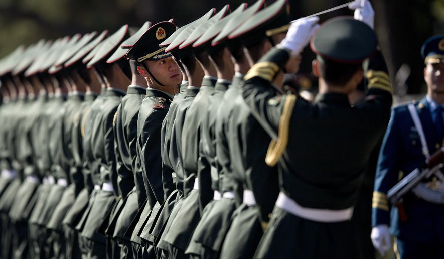 A member of a guard of honor looks at a rope as Chinese People's Liberation Army soldiers and officers use it to line up them in preparation for a welcome ceremony for visiting Indian Prime Minister Manmohan Singh outside the Great Hall of the People in Beijing Wednesday, Oct. 23, 2013. China and India signed a confidence-building accord Wednesday to cooperate on border defense following a standoff between armed forces of the two Asian giants in disputed Himalayan territory earlier this year. (AP Photo/Andy Wong)