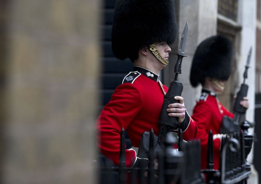 Two members of the Grenadier Guards come to attention outside St James's Palace, in London, Wednesday, Oct. 23, 2013. Prince William and his wife Kate have asked seven people to be godparents to their son, Prince George, who will be christened at a major royal family gathering Wednesday, palace officials said.  Queen Elizabeth II and her husband Prince Philip plan to attend the christening Wednesday at the Chapel Royal at St. James's Palace, along with Prince Charles, his wife Camilla, Prince Harry and other royals. (AP Photo/Alastair Grant)