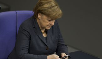 ** FILE ** The Jan. 20, 2011, file photo shows German Chancellor Angela Merkel using her mobile phone at the German Federal Parliament Bundestag in Berlin. The German Foreign Ministry said Thursday, Oct. 24, 2013, it has summoned the U.S. ambassador in the wake of allegations that American intelligence may have targeted Merkel's cellphone. (AP Photo/Gero Breloer)