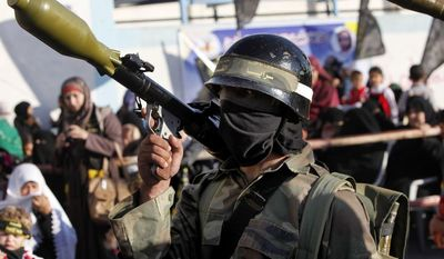 Islamic Jihad militants hold rocket-propelled grenades during a rally marking the 26th anniversary of the movement's foundation and marking the 18th anniversary of the death of the group's leader Fathi Shikaki, in Rafah Refugee Camp, southern Gaza Strip, Thursday, Oct. 24, 2013. (AP Photo/Adel Hana)