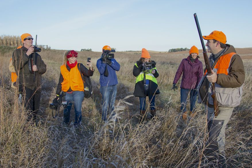 Cameras follow Sen. Ted Cruz, R-Texas, right, during a pheasant hunt hosted by Rep. Steve King, R-Iowa, on Saturday, Oct. 26, 2013, in Akron, Iowa. Cruz attended the Iowa GOP's annual fundraising dinner in Des Moines, Iowa, on Friday. (AP Photo/Nati Harnik)