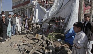 Afghans look at wreckage after a roadside bomb exploded on the outskirts of Kabul, Afghanistan, on Sunday, Oct. 27, 2013. An Afghan official and witnesses said the bomb, apparently targeting a group of soldiers, killed a civilian in a market in the capital as the soldiers and officers waited for a vehicle to take them to their workplace. (AP Photo/Rahmat Gul)