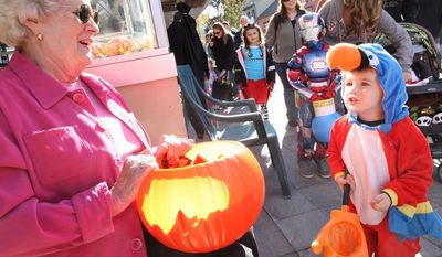 "Camden Coffman, 2, of Winchester, Va. shouts, ""Trick or Treat"" to Richard's Jewelry owner Jeanie Swisher during the Old Town Spooktacular event Saturday on the Loudoun Street Mall in Winchester, Va.  (AP Photo, The Winchester Star, Jeff Taylor)"