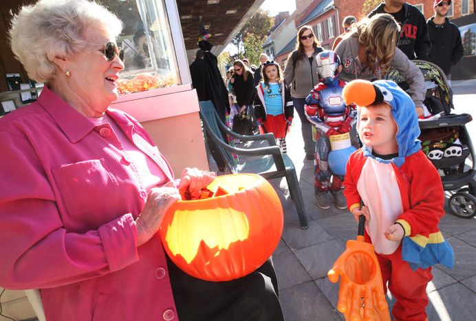 """Camden Coffman, 2, of Winchester, Va. shouts, """"Trick or Treat"""" to Richard's Jewelry owner Jeanie Swisher during the Old Town Spooktacular event Saturday on the Loudoun Street Mall in Winchester, Va.  (AP Photo, The Winchester Star, Jeff Taylor)"""