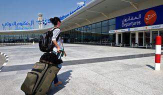 A traveler pulls her suitcase at the newly opened Al Maktoum International Airport in Dubai, United Arab Emirates, on Sunday, Oct. 27, 2013. (AP Photo/Patrick Castillo, Emarat Al Youm)