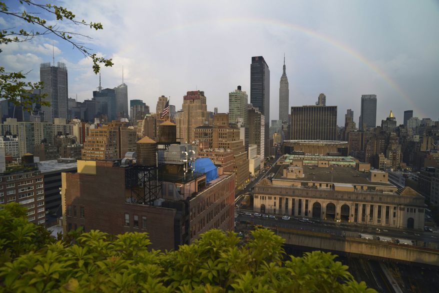 ** FILE ** A rainbow appears in the New York sky over the Empire State Building after a light rain lowered the 90-plus-degree temperature on July 20, 2013. (AP Photo/Patrick Sison)