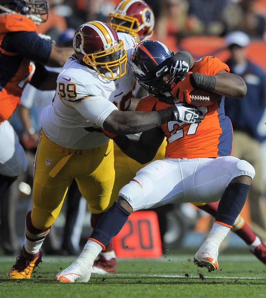 Denver Broncos running back Knowshon Moreno (27) is tackled by Washington Redskins defensive end Jarvis Jenkins (99) in the second quarter of an NFL football game, Sunday, Oct. 27, 2013, in Denver. (AP Photo/Jack Dempsey)