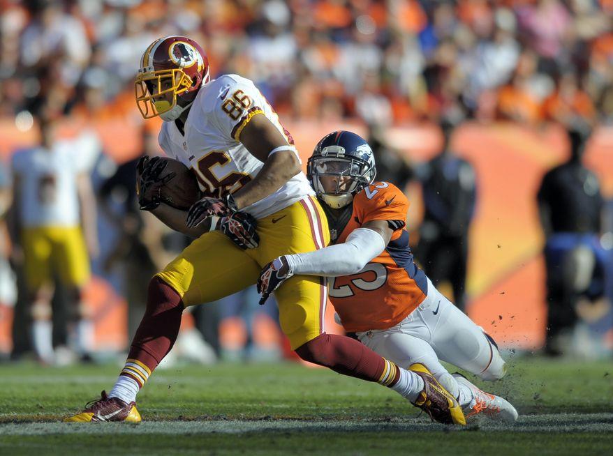 Washington Redskins tight end Jordan Reed (86) is tackled by Denver Broncos cornerback Chris Harris (25) in the second quarter of an NFL football game, Sunday, Oct. 27, 2013, in Denver. (AP Photo/Jack Dempsey)