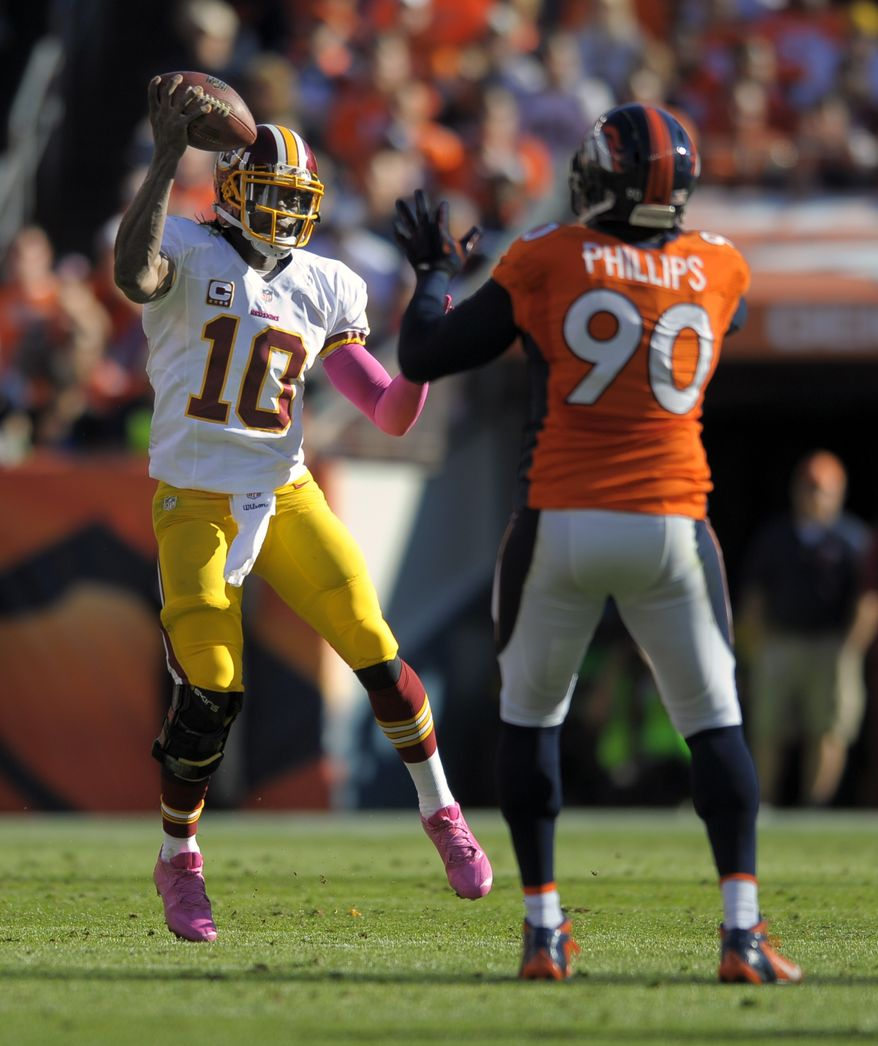 Washington Redskins quarterback Robert Griffin III (10) fakes a pass against Denver Broncos defensive end Shaun Phillips (90) in the second quarter of an NFL football game, Sunday, Oct. 27, 2013, in Denver. (AP Photo/Jack Dempsey)