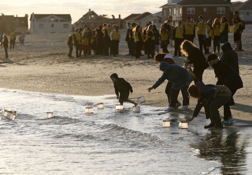 "Rockways residents float lanterns  containing handwritten personal messages in the water at the conclusion of ""Rockaways Rising: Hands Scross the Sand,"" commemorating the one year anniversary of Superstorm Sandy, Sunday, Oct. 27, 2013, in New York. The actual one year anniversary of Superstorm Sandy is Tuesday, Oct. 29. (AP Photo/Kathy Willens)"