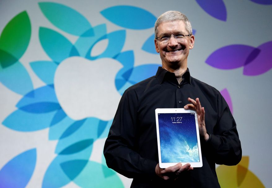 ** FILE ** In this Oct. 28, 2013, file photo, Apple CEO Tim Cook, holding the new iPad Air, said he remains confident the company can provide the products consumers want. (ASSOCIATED PRESS)