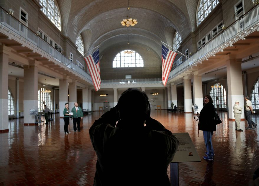 A visitor to the newly reopened Ellis Island stops to take a picture of the registry room in New York on Monday. Rebuilding and stormproofing the electrical and other networks without marring the 1900 Beaux-Arts-style building was a challenge to plan and is still a $21 million, 18-month work in progress. (Associated Press)