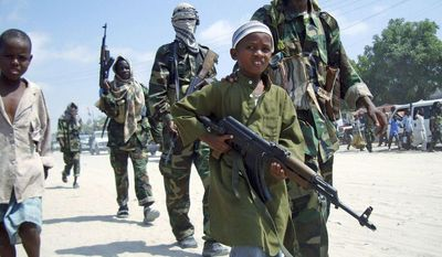 ** FILE ** A young boy leads the hard-line Islamist al-Shabaab fighters as they conduct a military exercise in northern Mogadishu's Suqaholaha neighborhood in Somalia. The country's continuous violence appears to have increased recruiting efforts of young fighters, minors who can easily be indoctrinated. (Associated Press)